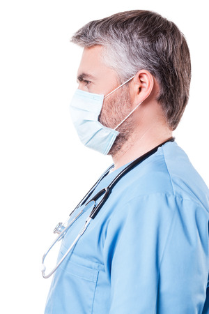 grey hair: Confident surgeon. Side view of mature grey hair doctor in surgical mask looking at camera while standing isolated on white