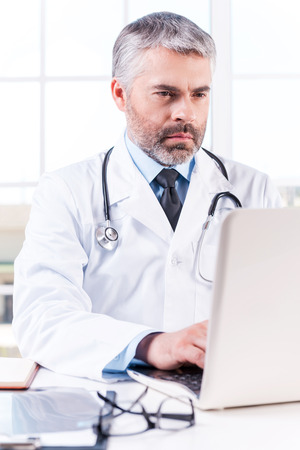 grey hair: General practitioner. Mature grey hair doctor working on laptop while sitting at his working place 스톡 사진
