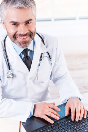 one senior man only: Confident and experienced doctor. Top view of confident mature grey hair doctor working on laptop and smiling while sitting at his working place Stock Photo