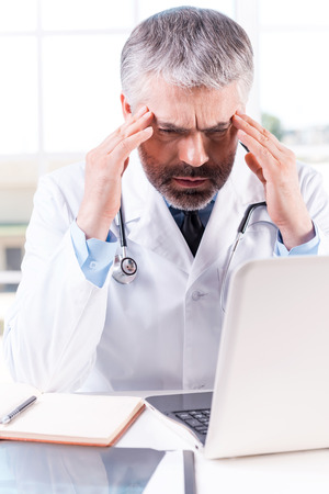 Stressed and tired doctor. Depressed mature grey hair doctor touching his head with hands while sitting at his working place photo