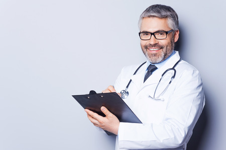 doctor writing: Writing prescription. Cheerful mature doctor looking at camera and smiling while writing something at his clipboard and standing against grey background
