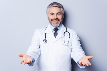 hands out: Cheerful doctor. Cheerful mature grey hair doctor looking at camera while stretching out hands and smiling while standing against grey background