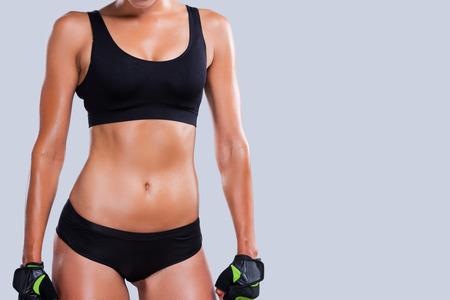 Cuerpo perfecto. Primer plano de mujer joven y deportivo con gran prestigio cuerpo contra el fondo gris Foto de archivo