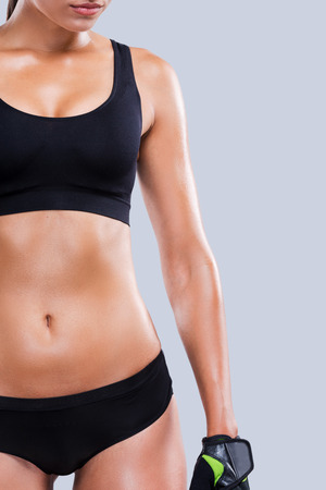 body curve: Keeping her body in shape. Close-up of young sporty woman with perfect body standing against grey  Stock Photo
