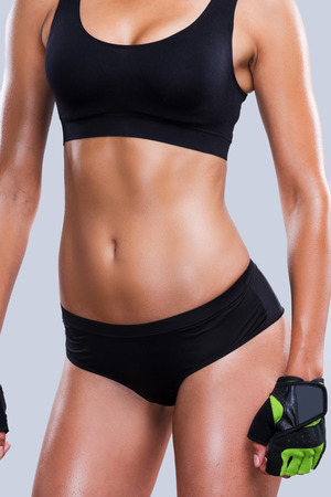 Ajuste de curvas. Primer plano de mujer joven y deportivo con un cuerpo perfecto de pie contra gris