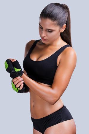スポーツ トレーニングの準備。完璧なボディの彼女を調整する美しい若いスポーティな女性スポーツ手袋グレーに対して立っている間