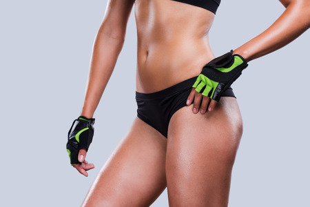 perfect fit: Fit curves. Close-up of young sporty woman with perfect body holding hand on hip while standing against grey background