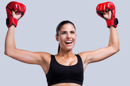 I am a winner! Happy young sporty woman in boxing gloves keeping arms raised while standing against grey  photo