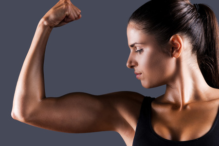bicep: Perfect bicep. Beautiful young sporty woman examining her bicep while standing against grey  Stock Photo