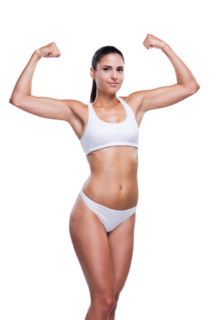 only the biceps: Proud of her fit body. Beautiful young woman in white bra and panties showing her biceps and smiling while standing isolated on white