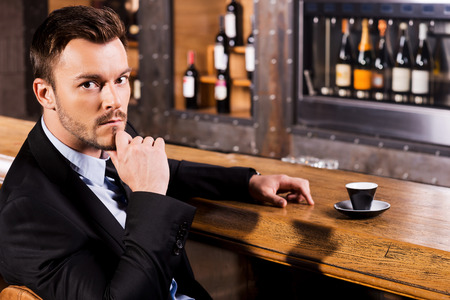 bar counter: Relaxing with cup of fresh coffee. Confident young man in formalwear sitting at the bar counter and looking at camera with cup of fresh espresso standing near him Stock Photo