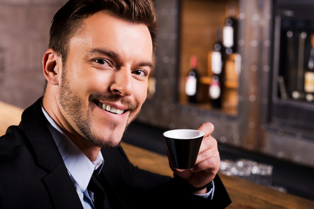 Inspired by cup of fresh coffee. Confident young man in formalwear drinking coffee and smiling while sitting at the bar counter photo