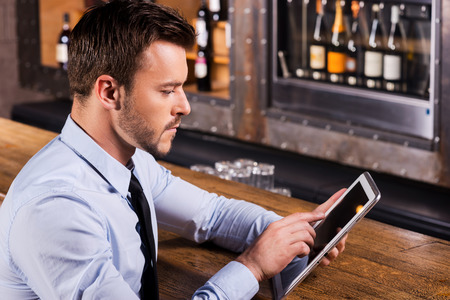 Always staying in touch. Confident young man in shirt and tie sitting at the bar counter and working on digital tablet photo