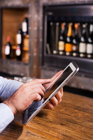 vertical bars: Taking advantages of free Wifi. Close-up of man in blue shirt working on digital tablet while sitting at the bar counter