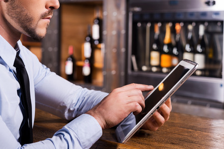 vertical bar: Surfing web in bar. Close-up of man in shirt and tie working on digital tablet while sitting at the bar counter