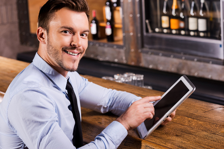 side bar: Businessman in bar. Handsome young man in shirt and tie working on digital tablet and smiling while sitting at the bar counter