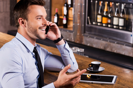 Good talk with friend. Side view of happy young man in shirt and tie talking on the mobile phone and gesturing while sitting at the bar counter photo