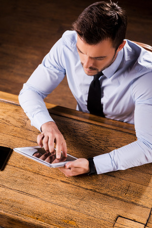 surfing the internet: Businessman at the bar counter. Top view of confident young man in shirt and tie sitting at the bar counter and working on digital tablet