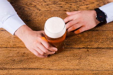 bar top: Beer time. Top view of male hands holding beer glass on the bar counter  Stock Photo