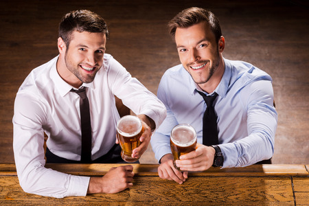 Relaxing at Friday night. Top view of two cheerful young men in shirt and tie holding glasses with beer and smiling while sitting at the bar counter  photo