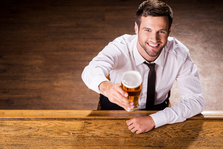 bar top: Relaxing with glass of fresh beer. Top view of handsome young man in shirt and tie holding glass with beer and smiling while sitting at the bar counter