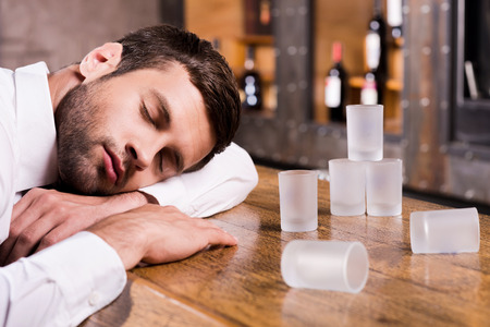 getting away from it all: Drunk again. Drunk man in white shirt leaning at the bar counter and sleeping while empty glasses standing near him