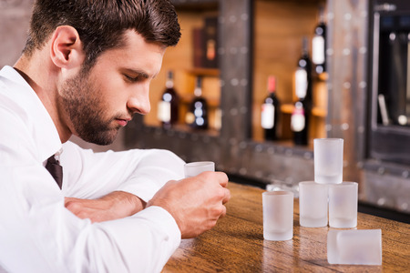 drinking problem: Drinking again. Depressed drunk man in shirt and tie leaning at the bar counter and sleeping while empty glasses standing near him  Stock Photo