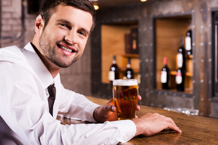 Enjoying cold and fresh beer. Side view of handsome young man in shirt and tie holding glass with beer and smiling while sitting at the bar counter  photo
