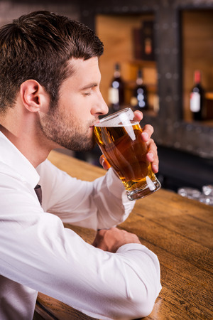 Enjoying his favorite lager. Side view of handsome young man drinking beer while sitting at the bar counter  photo