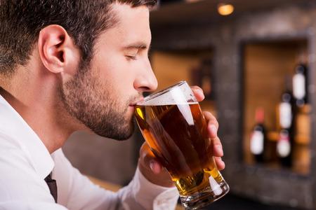 hombre tomando cerveza: Hombre bebiendo cerveza. Vista lateral de la joven y apuesto hombre de beber cerveza mientras estaba sentado en la barra del bar Foto de archivo