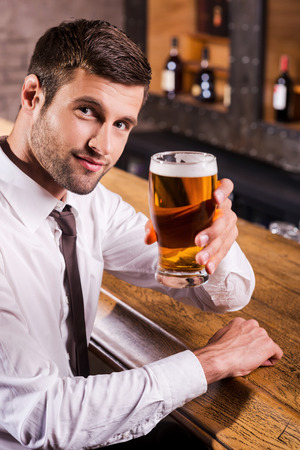 Cheers! Handsome young man in shirt and tie toasting with beer and looking at camera while sitting at the bar counter  photo