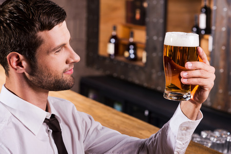 Enjoying the best beer ever. Side view of handsome young man in shirt and tie examining glass with beer and smiling while sitting at the bar counter  photo
