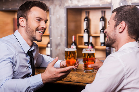 Friday night fun. Two cheerful young men in shirt and tie talking to each other and gesturing while drinking beer at the bar counter  photo