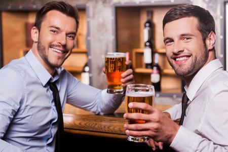 jornada de trabajo: Día de relajación después de trabajar duro. Dos jóvenes felices en camisa y corbata con las copas de cerveza y sonriendo mientras está sentado en la barra del bar