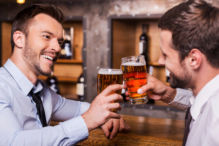 Having a pint with friend. Two cheerful young men in shirt and tie toasting with beer while sitting together at the bar counter  photo