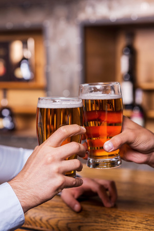 Cheers! Close-up of two men toasting with beer at the bar counter  photo