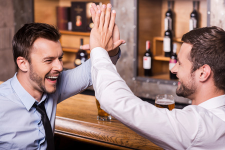 congratulating: Celebrating success together. Two cheerful young men in shirt and tie talking to each other and gesturing while drinking beer at the bar counter
