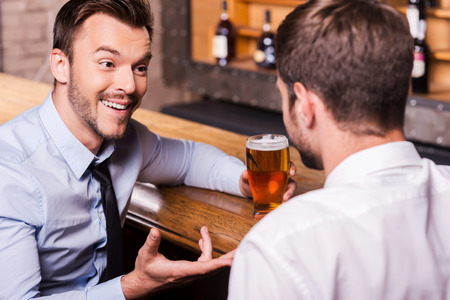 Sharing beer with good friend. Two cheerful young men in shirt and tie talking to each other and gesturing while drinking beer at the bar counter  photo