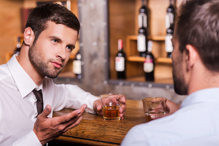 Spending night in bar. Two confident young men in shirt and tie talking to each other and gesturing while drinking whisky at the bar counter  photo