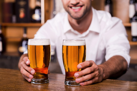 quench: Quench your thirst! Close-up of handsome young male bartender in white shirt stretching out glasses with beer and smiling while standing at the bar counter  Stock Photo