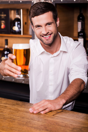 let out: Let me quench your thirst! Handsome young male bartender in white shirt stretching out glass with beer and smiling while standing at the bar counter