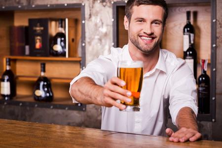 hombre tomando cerveza: Déjame saciar su sed! Camarero de sexo masculino joven feliz en camisa blanca estirar vaso con cerveza y sonriendo mientras está de pie en la barra del bar