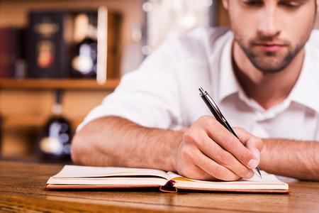 hombre escribiendo: Due�o del bar Confident. Primer plano de camarero masculino joven y guapo en camisa blanca que se inclina en la barra del bar y escribir algo en el bloc de notas