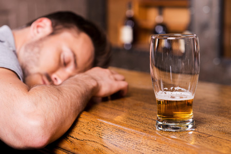 near beer: Drunk again. Drunk male customer leaning at the bar counter and sleeping while glass with beer standing near him  Stock Photo