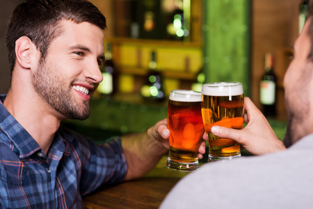 Friday night out. Two cheerful young men toasting with beer and smiling while sitting together at the bar counter  photo