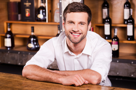 bars: Cheerful bartender. Handsome young male bartender in white shirt leaning at the bar counter and smiling