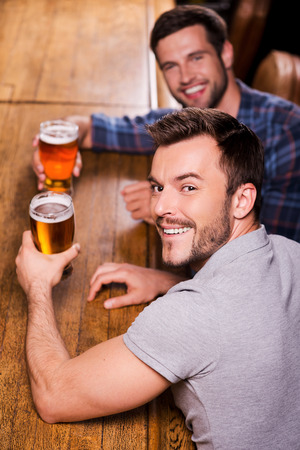 draught: Friends in bar. Top view of two happy young men drinking beer at the bar counter and smiling Stock Photo