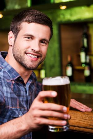 hombre tomando cerveza: ¡Salud! Apuesto joven brindando con cerveza y mirando a cámara con una sonrisa mientras estaba sentado en la barra del bar