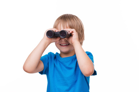 boys only: Curious little boy. Cheerful little boy looking through binoculars and smiling while standing isolated on white Stock Photo