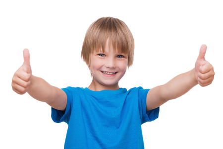 Thumbs up! Happy little boy showing his thumbs up and smiling while standing isolated on white Stock Photo